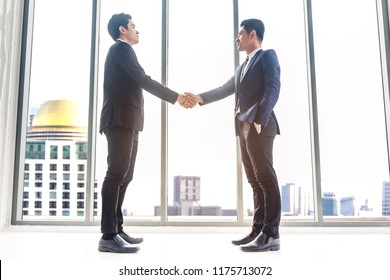 Image two business partners in black elegant suit successful handshake and talking together while discussing new strategy in modern office background.Partnership approval and thanks gesture concept