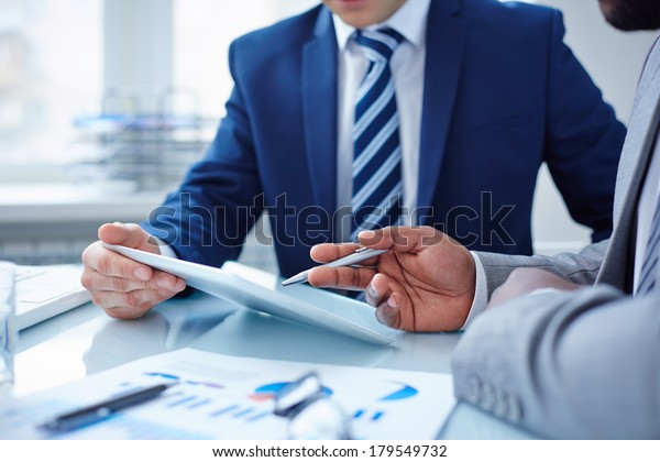 Image of two businessmen discussing computer project