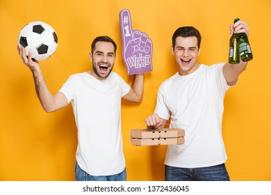 Image of two caucasian men supporter 30s in white t-shirts holding soccer ball and number one fan hand glove while standing isolated over yellow background