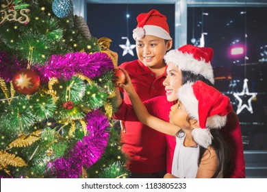 Image of two children and  their mother decorating a tree to prepare Christmas day. Shot at home