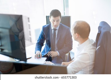 Image of two corporate businessmen discussing a bisiness problem at meeting in modern trading office. Businesspeople sitting at the boardroom and discussing business-plan.
