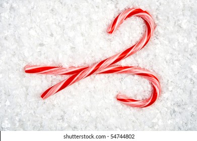 Image of two crossed candy canes lying in the snow