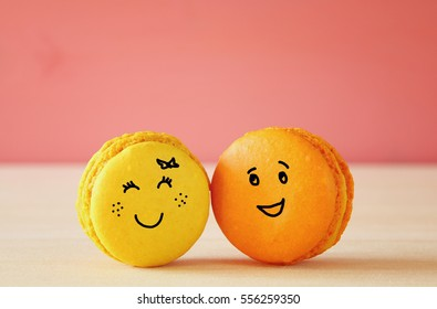 Image of two cute macaroons with drawn smiley faces on wooden table. Best friend concept