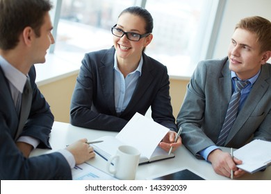 Image of two employees listening to young man at interview
