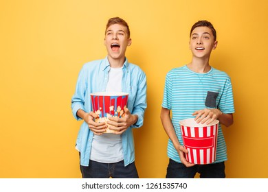 Image of two excited beautiful teenagers, guys watching an interesting movie and eating popcorn
