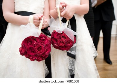 Image of two flower girls with red rose bouquet