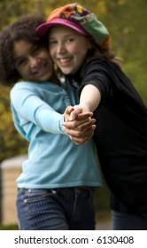 image of two girls of different ethnicities...shallow depth of field with only hands in focus