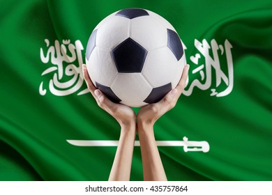 Image of two hands lifting a soccer ball with flag background of Saudi Arabia