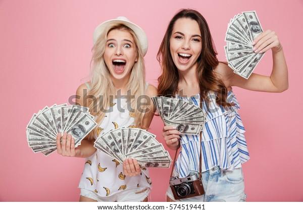 Imagen de dos felices mujeres emocionales paradas aisladas sobre fondo rosado sosteniendo dinero.