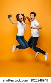 Image of two joyful man and woman 20s making selfie on cell phone while jumping and gesturing together, over yellow background