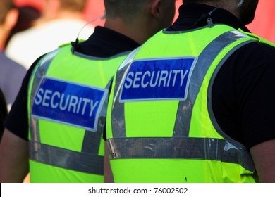 Image of two male security Guards with bright tops on.
