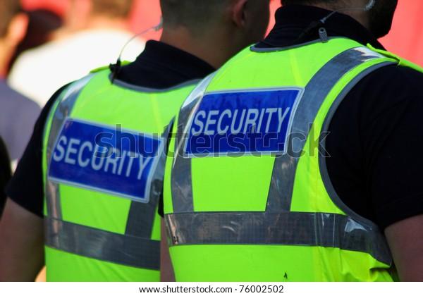 Photo de deux gardes de sécurité masculins avec des hauts-parleurs brillants allumés.