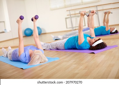 Image of two mature females doing exercise with barbells in sport club