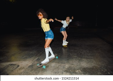 Image of two multinational girls in streetwear smiling and riding skateboards at night outdoors