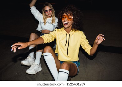Image of two multinational girls in streetwear smiling and riding on skateboards at night party outdoors