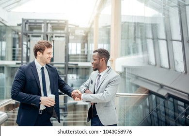 Image of two multiracial businessmen handshaking in modern office for end of great deal