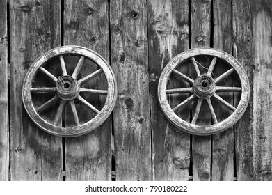 An image of two old wooden wheels on the background of an old wooden shed wall. A black and white version