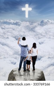Image of two parents and their children standing on the cliff while looking at a cross sign on the sky