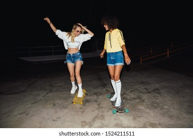 Image of two stylish girls in streetwear smiling and riding skateboards at night outdoors