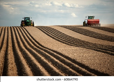 Image of two Tractors planting potatoes in the fertile farm fields of Idaho.