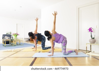 An image of two women doing yoga at home