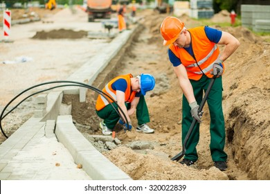 Image of two workers on a road construction