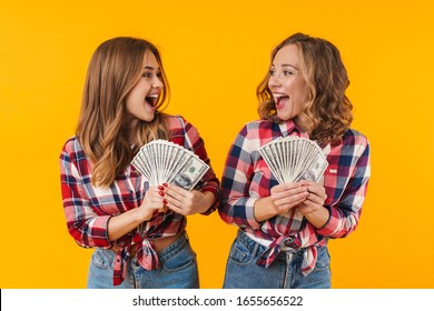 Image of two young beautiful girls wearing plaid shirts holding dollar banknotes isolated over yellow background
