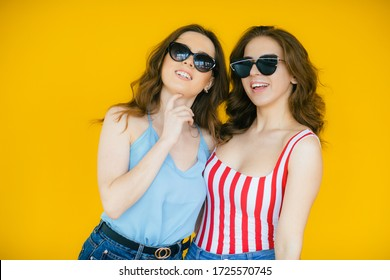 Image of two young beautiful girls wearing plaid shirts smiling and having fun isolated over yellow background