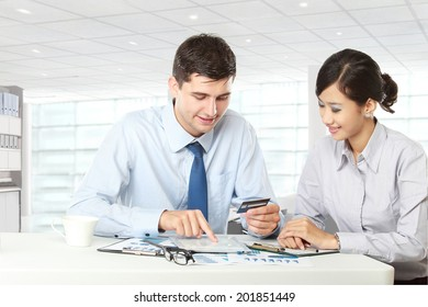 Image of two young business partners using touchpad and credit card at meeting