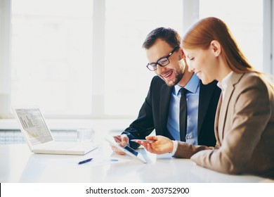 Image of two young business partners using touchpad at meeting