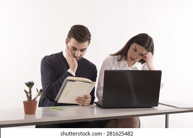 Image of two young business partners using laptop computer