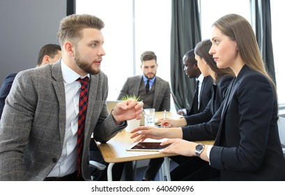 Image of two young business people interacting at meeting in office