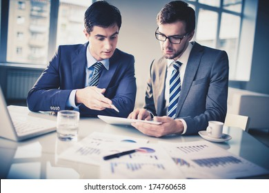 Image of two young businessmen discussing new project in office