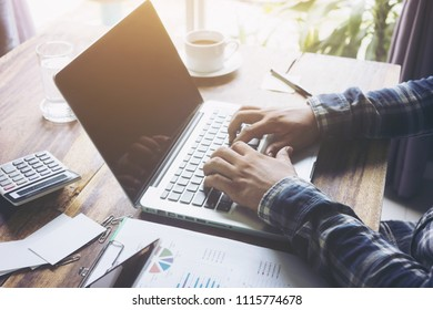 Image of two young businessmen using laptop computer. Male hand typing on laptop keyboard while sitting in coffee shop indoors, selective focus, soft focus