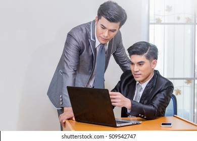 Image of two young businessmen using notebook at meeting