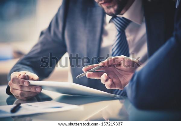 Bild von zwei jungen Geschäftsleuten mit Touchpad bei der Besprechung