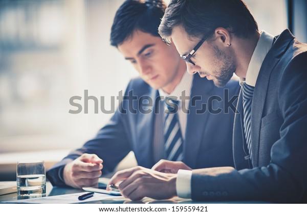 Imagem de dois jovens empresários usando touchpad na reunião