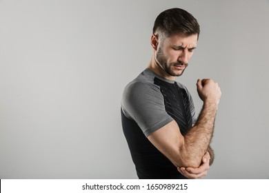 Image of unhappy athletic sportsman with injury standing while working out isolated over gray background