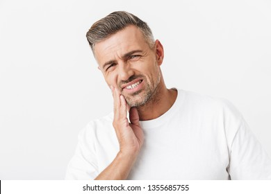 Image of unshaved man 30s with bristle wearing casual t-shirt touching his cheek and suffering from toothache isolated over white background