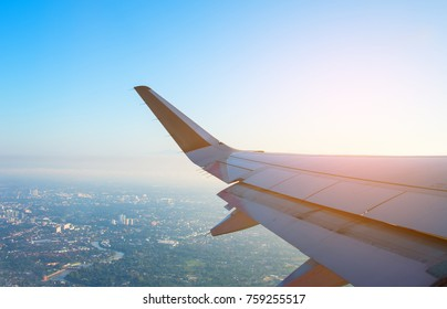 image of view from plane window to see wing and blue sky for background.