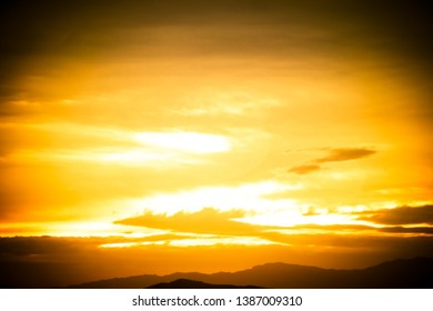 An image with a vignette of the golden colors of sunset shinning through distant clouds with mountain peaks.