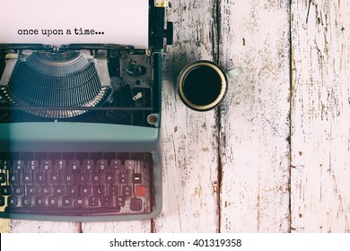 "image of vintage typewriter with phrase ""once upon a time"" and cup of coffee on wooden table, retro filtered"