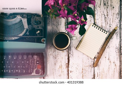 """image of vintage typewriter with phrase """"once upon a time"""", blank notebook, cup of coffee on wooden table"""