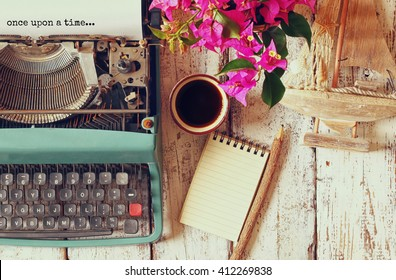 "image of vintage typewriter with phrase ""once upon a time"", blank notebook, cup of coffee and old sailboat on wooden table"