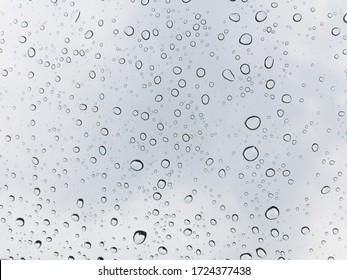 Image of water droplets on a clear glass surface during heavy rain.