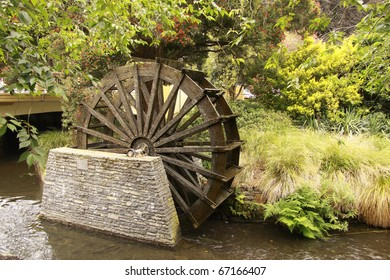 image of a water wheel beside river at avon river, christchurch new zealand