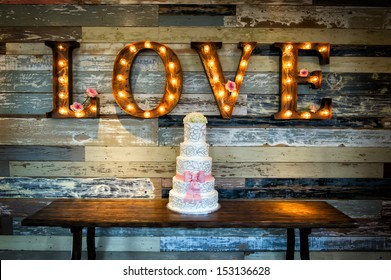 Image of a wedding cake with the word love as signage on a rustic background