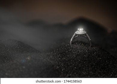 Image of wedding ring on a black sand background. Close up of an elegant engagement diamond ring on a black sand background.