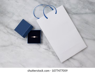 Image of wedding rings in a blue gift box, with white blank package. Empty place for an inscription.
