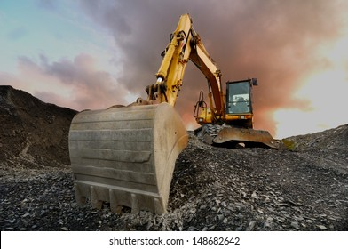Image of a wheeled excavator on a quarry tip